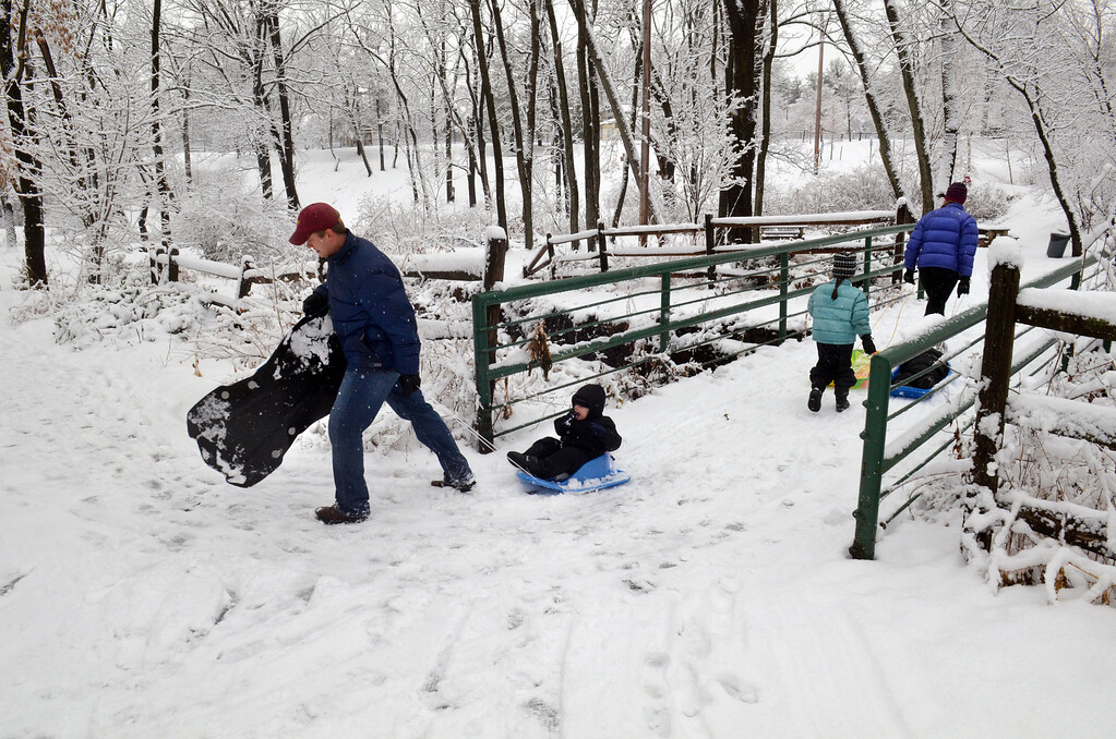 Description of . Parents and children in Whites Road Park in Lansdale during a morning snowfall.  (The Reporter/Geoff Patton)