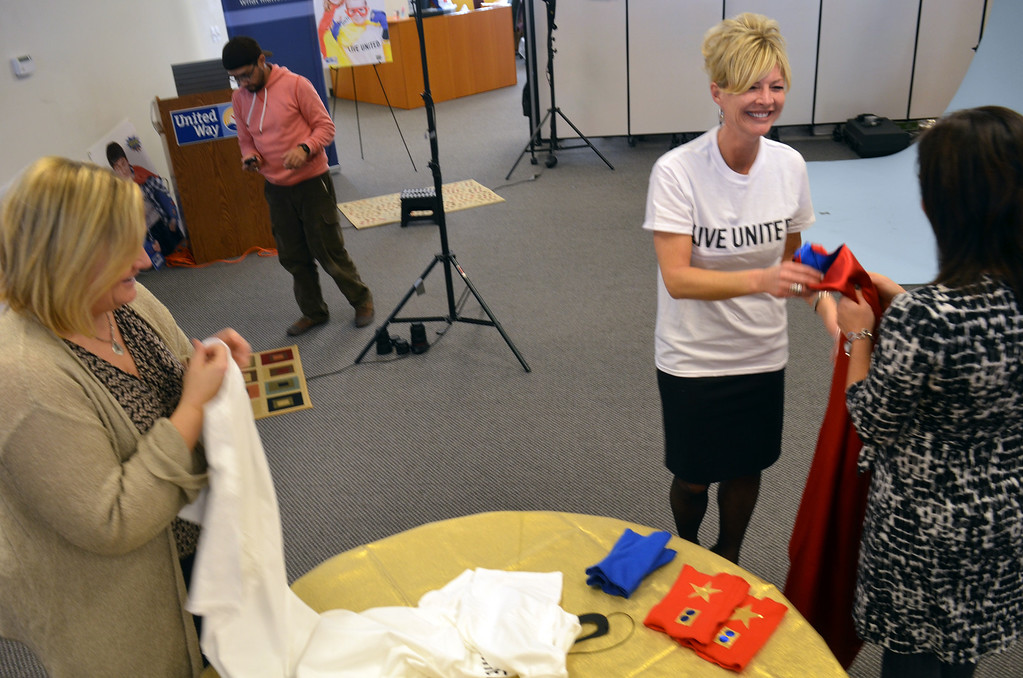 Description of . Robyn Garis hands in her cape following a photo shoot for North Penn United Way's third annual Superheroes United for Kids event.   At left is NPUW director of communications Stephanie Simon .   Friday, January 24, 2014.  Photo by Geoff Patton
