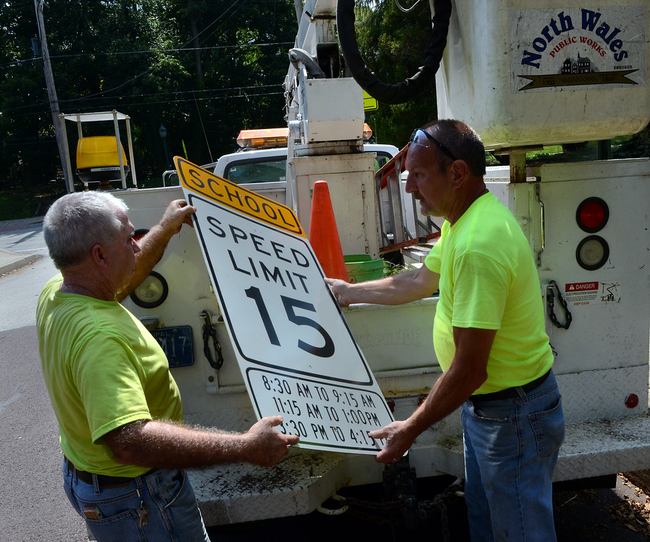 Description of . North Wales Public Works employees Joe Rouse ,L, and George Keriick change the traffic signs along Summit Ave near North Wales Elementary School on Wednesday afternon August 27,2014. Photo by Mark C Psoras/The Reporter