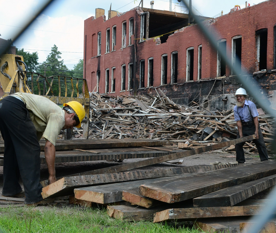 Description of . Workers remove floor planks from the old Penn Pants Factory in Sellersville during demolition at the site on Tuesday July 22,2014.Photo by Mark C Psoras/The Reporter
