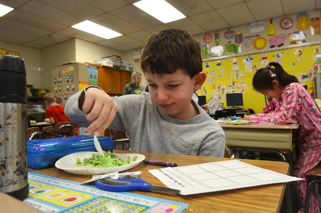 Description of . First grader Caden Langeveld samples green eggs and ham in a classroom at Montgomery Elementary School.   The snack was served as part of Reading Week activity held annually to celebrate Dr. Seuss's birthday.    Friday, March 7, 2014.   Photo by Geoff Patton