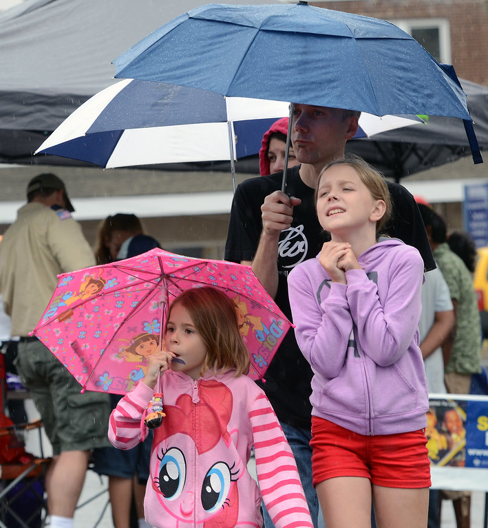 Description of . The Braster family hudle under umbrellas as rain falls during the Lansdale Founders Day  celebration on Saturday August 23,2014. Photo by Mark C Psoras/The Reporter