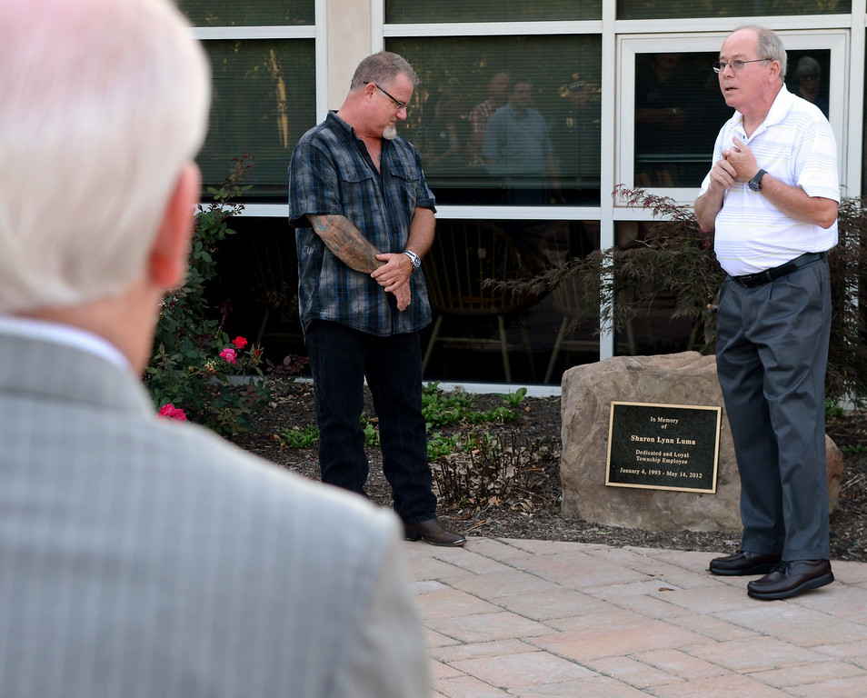 Description of . Towamencin Township Board of Supervisors Chairman Daniel M. Littley, Jr.,R, speaks as memorial stone and plaque are dedicated to Sharon Luma, a former assistant to the Towamencin Township manager,who was killed in a motorcycle accident. Tim Luma ,L, her husband  along with friends and Towamencin Township officiials gathered for the ceremony at the township building on Wednesday August 27,2014. Photo by Mark C Psoras/The Reporter