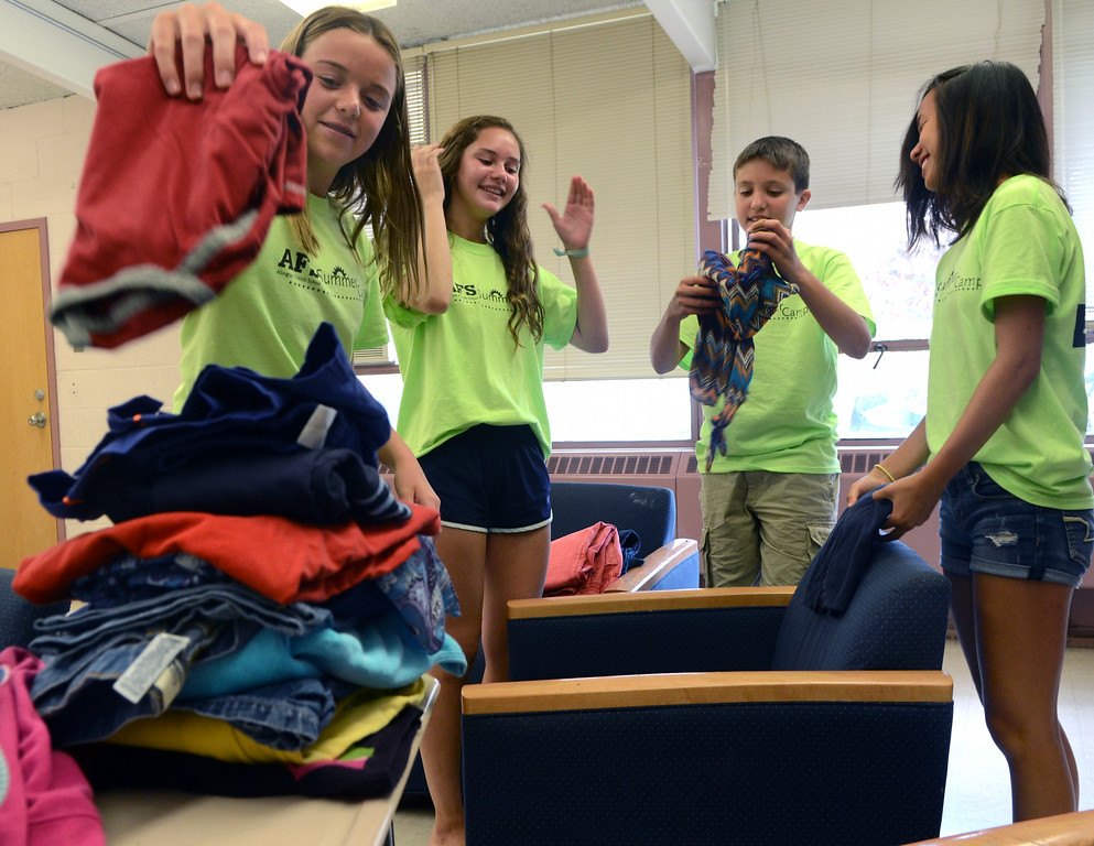 Description of . Abington Friends School Summer Camp Counslers in Training (L-R)Emma Turner,Emma Giddings,Nicholas DiBello and Mia Panzek  fold clothes for donation as part of their community service programs at the school on Tuesday August 8,2014. Photo by Mark C Psoras/The Reporter