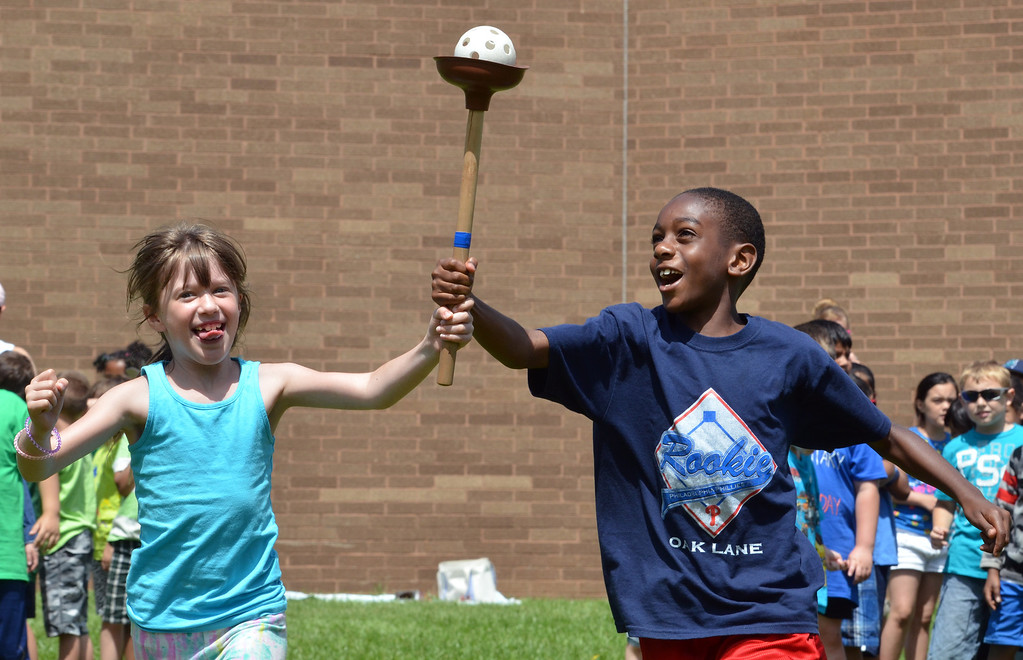 Description of . Second graders Taylor Orndorff, left, and Mark Cobbs compete  in the torch relay during Olympics Day at Hatfield Elementary School.   Friday,  June 6, 2014.   Photo by Geoff Patton