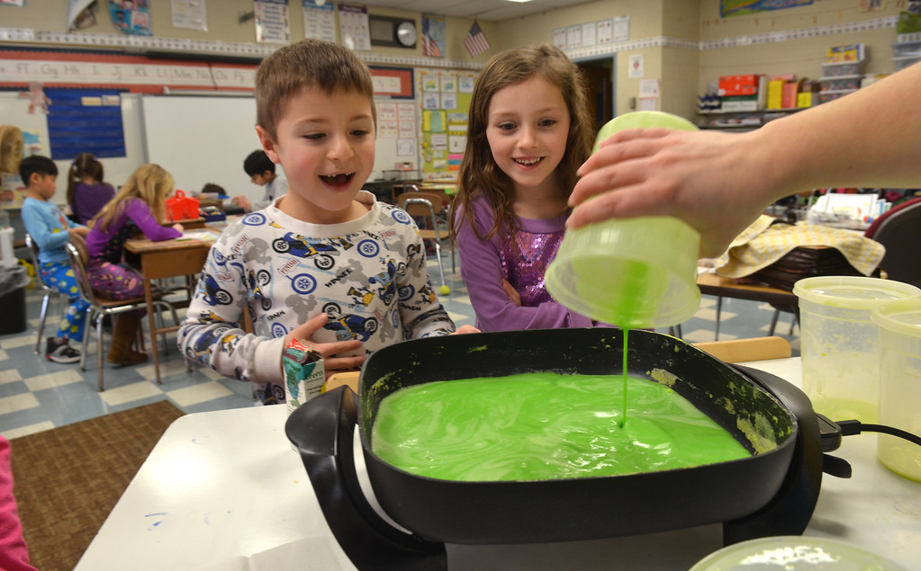 Description of . Justin Smilowitz, left, and Hailey Merritt watch as first grade teacher Danielle Scheer pours green scambled eggs into a pan at Montgomery Elementary School.   The green eggs and ham were served as part of Reading Week activity held annually to celebrate Dr. Seuss's birthday.   Friday, March 7, 2014.   Photo by Geoff Patton