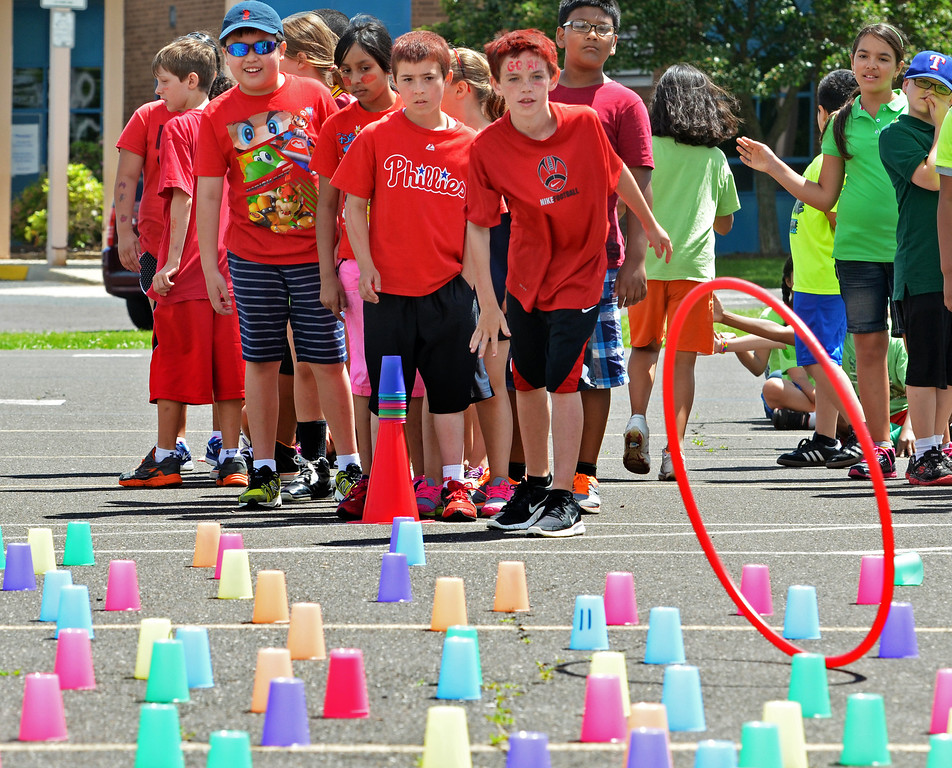 Description of . Fourth graders play candyland, one of the Olympics Day games at Hatfield Elementary School.   Friday, June 6, 2014.   Photo by Geoff Patton