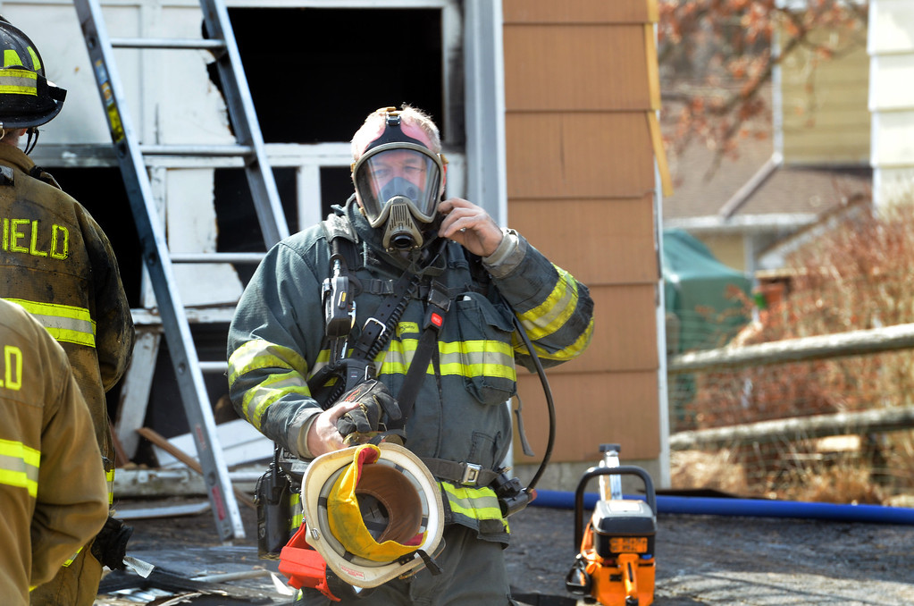 Description of . A firefighter exits  a house fire on Adams Avenue  Thursday in Hatfield.   (The Reporter/Geoff Patton)
