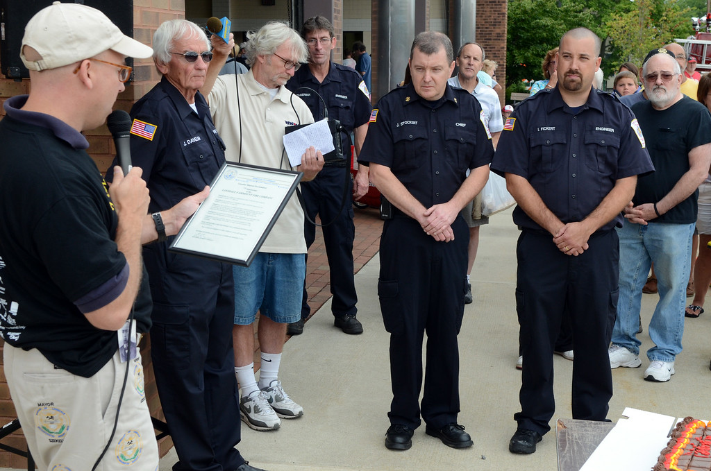 Description of . Lansdale Mayor Andy Szekely ,L, presents a proclamation to Fairmount Fire Company Chief Joe Stockert (center) President Ian Fickert (R) and Fire Marshall Jay Davelar (2nd from L) during the Lansdale Founders Day  celebration and on Saturday August 23,2014. Photo by Mark C Psoras/The Reporter