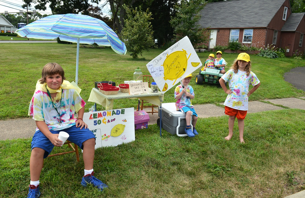 Description of . Sporting tie-dyed shirts and yellow hats, young members of the neighboring Whiting and Wilson families wait for customers at their lemonade stand on Greenwood Road in Lansdale.   From left, Josh Wilson,  Griffin Whiting, Violet Whiting, Elisha Wilson, and Ella Whiting.   The youngsters combined the first letters of their last names to call the stand  'W&W Lemonade'  cookies and brownis.   They are earning money for their upcoming trip to Wildwood, New Jersey.     Monday, July 21, 2014.    Photo by  Geoff Patton