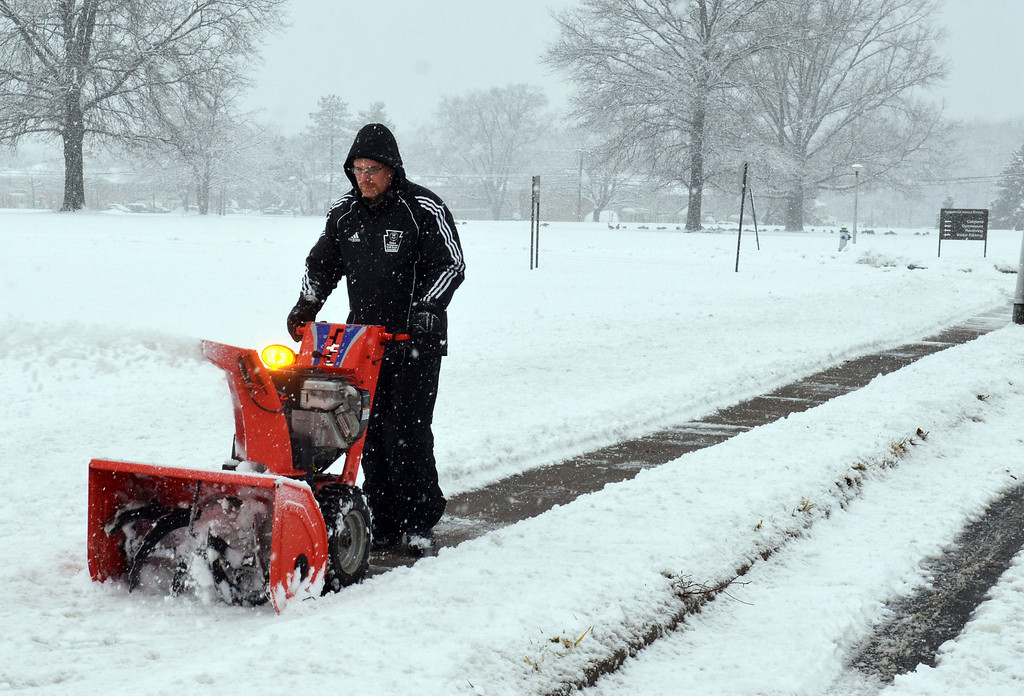 Description of . Joe Dizio clears snow  from sidewalk in front of Pennbrook Middle School.  (The Reporter/Geoff Patton)