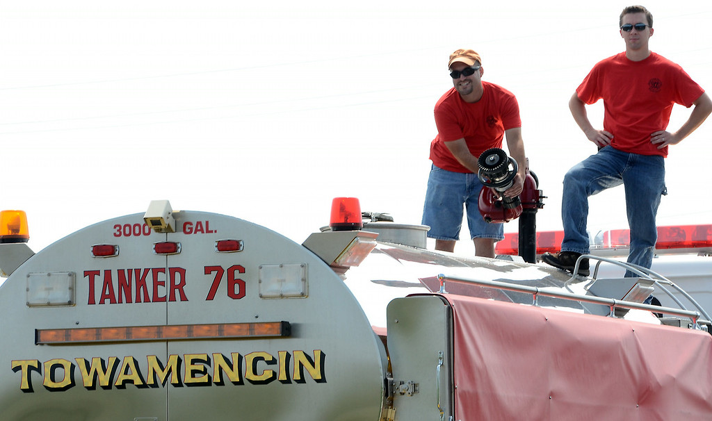 . Towamencin Fire Company members adjust a hose on a tanker during the 14th annual Montgomery County Fifth Fire District Water Battle held at the Towamencin Firehouse on Saturday morning July 12,2014.Photo by Mark C Psoras/The Reporter