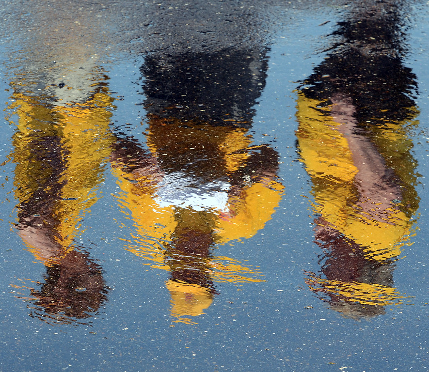 . Officials of14th annual Montgomery County Fifth Fire District Water Battleare reflected in a puddle as the tabulate scores during the competition held at the Towamencin Firehouse on Saturday morning July 12,2014.Photo by Mark C Psoras/The Reporter