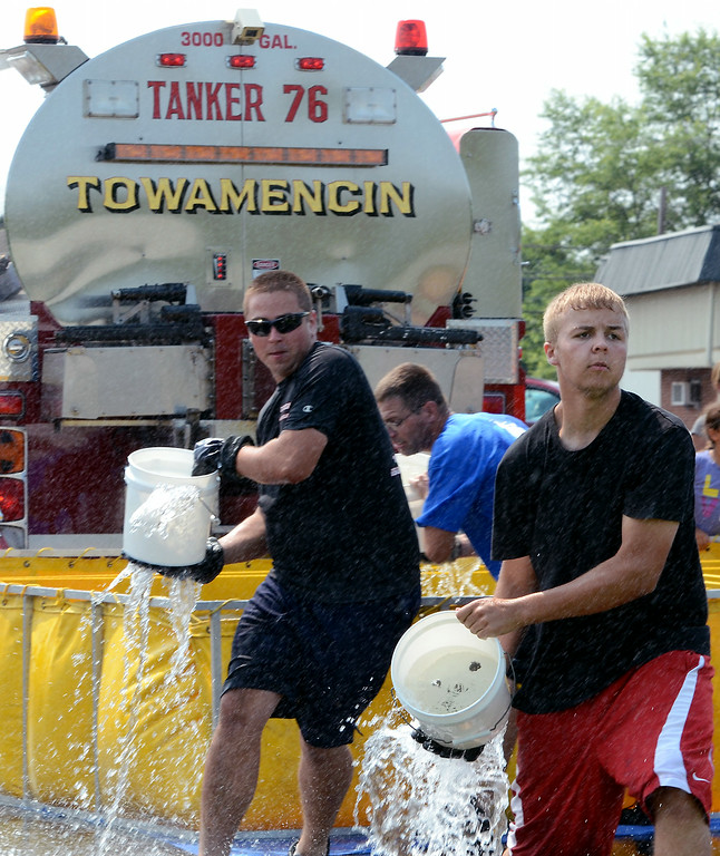 . Hatfield  Fire Company members take part in a bucket brigade competition during the 14th annual Montgomery County Fifth Fire District Water Battle held at the Towamencin Firehouse on Saturday morning July 12,2014.Photo by Mark C Psoras/The Reporter