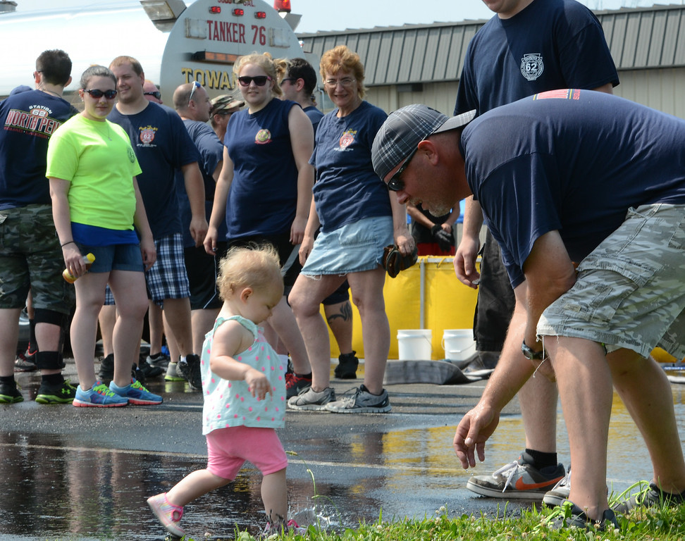 . North Penn Fire Company member Stephen Forbes splashes in a puddle with Payton Burkart ,16 mos, during the 14th annual Montgomery County Fifth Fire District Water Battle held at the Towamencin Firehouse on Saturday morning July 12,2014.Photo by Mark C Psoras/The Reporter
