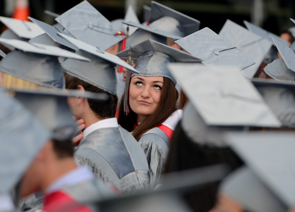 . A Upper Dublin High School Class of 2014 member peers up to the sky as storm clouds gather during their Commencement Ceremony at the school on Tuesday evening June 10,2014. Photo by Mark C Psoras/The Reporter