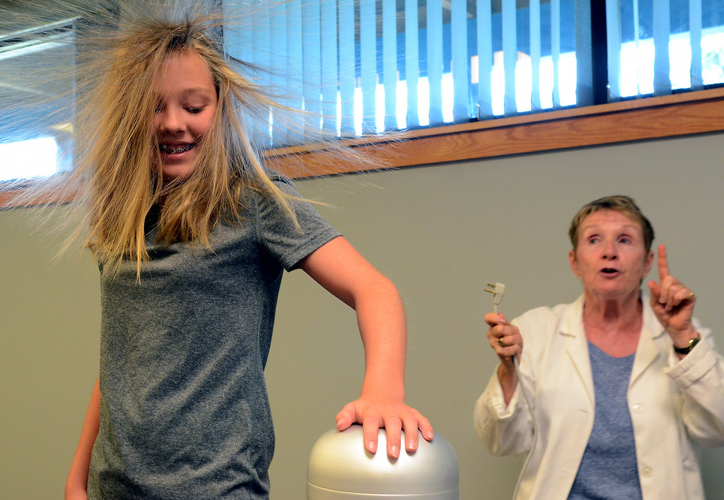 . Teacher Rosemary Carr watches as Lauren Atchley\'s hair stands up as she touches a Van Der Graff Generator as she leads children conducting experiments in Physical Science & Eelectricity during the GSK Science in Summer event at the Perkasie Branch of the Free Library of Bucks County on Tuesday July 22,2014.Photo by Mark C Psoras/The Reporter