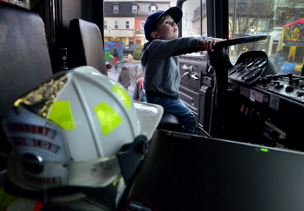 . Children check out a Fairmount Fire Company truck during First  Friday in Lansdale on a chilly and wet evening April 4,2014.  (The Reporter/Mark C. Psoras)