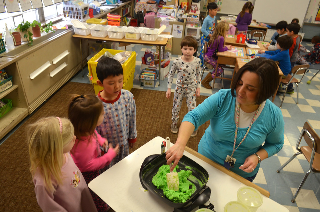 . Teacher Danielle Scheer prepares green scrambled eggs in a first grade classroom at Montgomery Elementary School.   The green eggs and ham were served as part of Reading Week activity held annually to celebrate Dr. Seuss\'s birthday.   Friday, March 7, 2014.   Photo by Geoff Patton