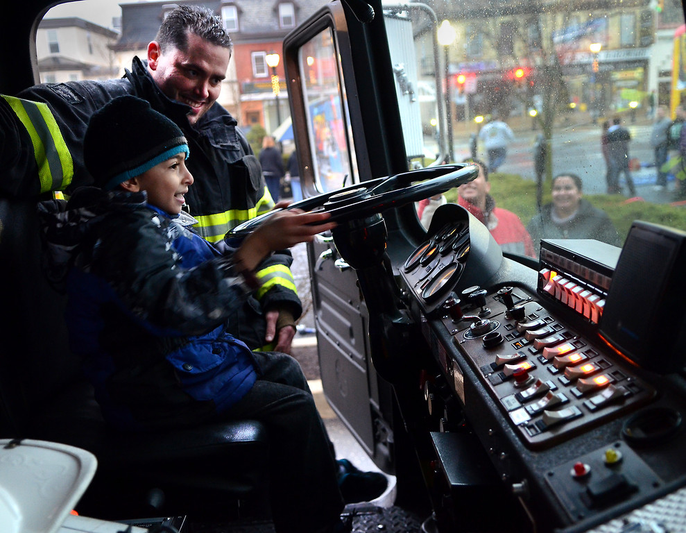 . Fairmount Fire Company Assistant Chief Jake Slavens shows Rafauel Armanius ,6, the inside of a fire truck during First  Friday in Lansdale on a chilly and wet evening  April 4,2014. (The Reporter/Mark C. Psoras)