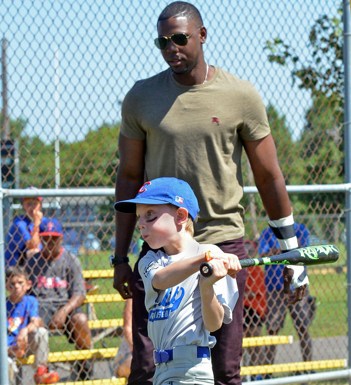 . Seven-year-old Nolan Pounds takes a swing under the watchful eye of Phillies outfielder John Mayberry Jr. at  Nor Gwyn baseball camp in Upper Gwynedd.    His visit was arranged by Sanctuary United Methodist Church pastor Jim Carver, who is friends with Phillies pastor Rich Sparling.   Mayberry talked his life in baseball, spirituality, and answered the youngsters\' many questions.    Friday,  July 25, 2014.   photo by Geoff Patton