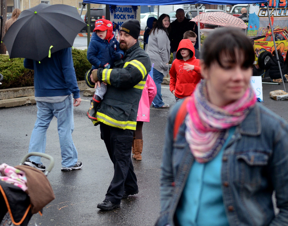 . Fairmount Fire Company President  Ian Fickert holds his son Camryn (center) check out games and activities during First  Friday in Lansdale on a chilly and wet evening  April 4,2014. (The Reporter/Mark C. Psoras)