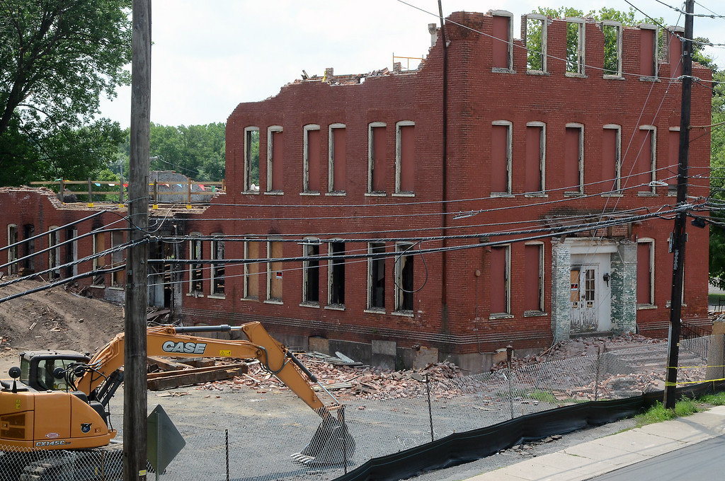 . Workers remove floor planks from the old Penn Pants Factory in Sellersville during demolition atthe site on Tuesday July 22,2014.Photo by Mark C Psoras/The Reporter