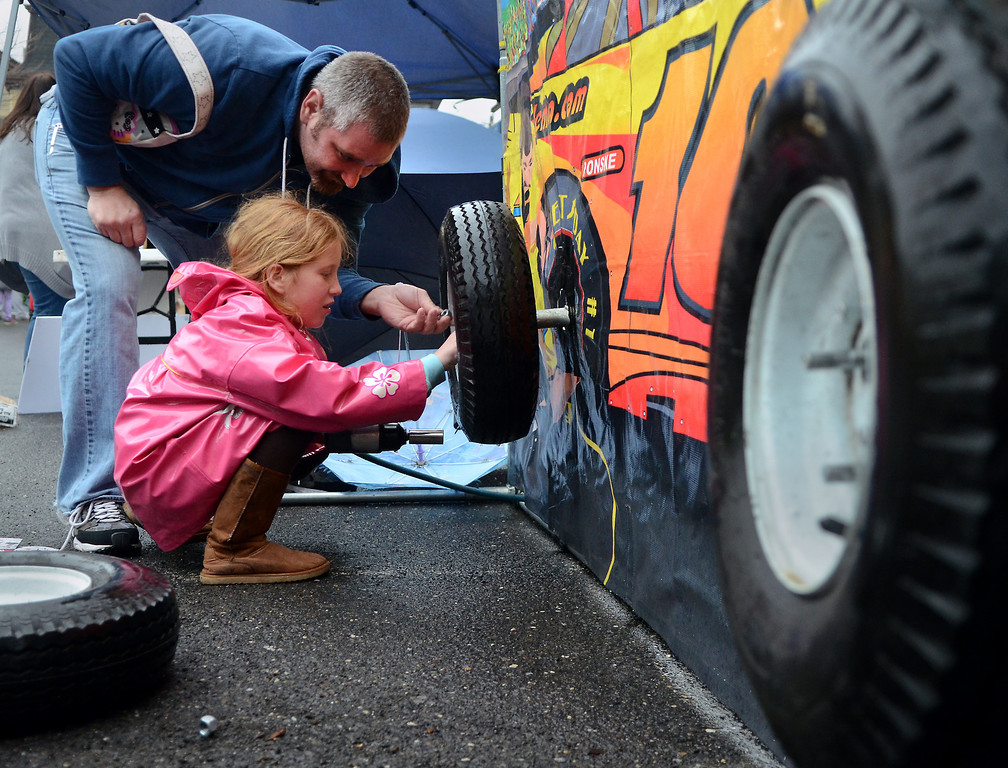 . Scott Nicholson and his daughter Drea ,8, check out games and activities during First  Friday in Lansdale on a chilly and wet evening  April 4,2014.  (The Reporter/Mark C. Psoras)
