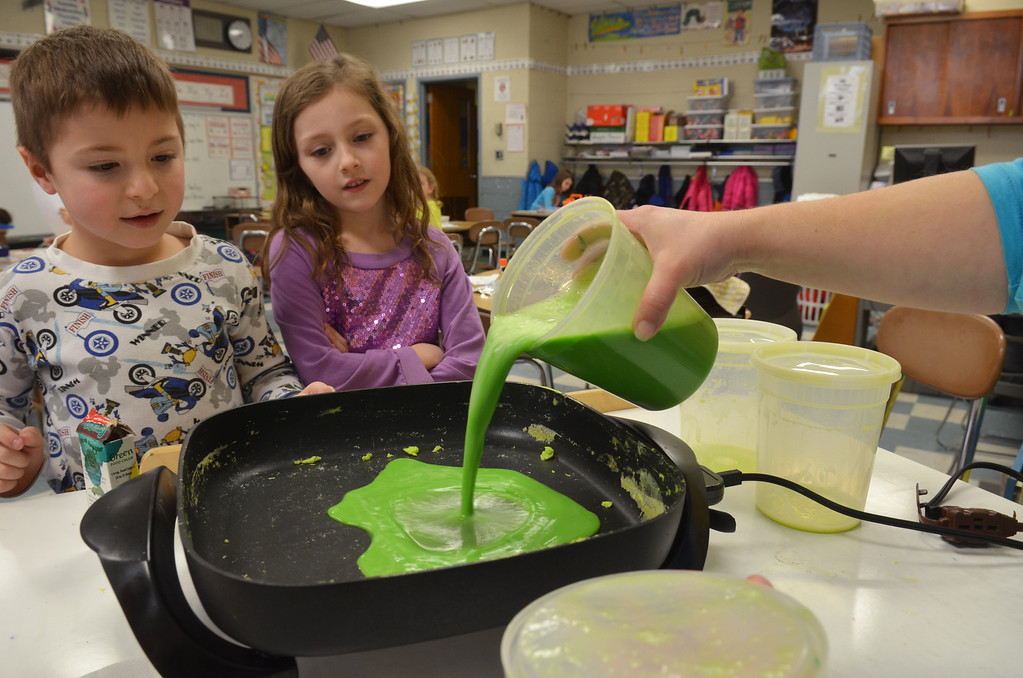 . Justin Smilowitz, left, and Hailey Merritt watch as first grade teacher Danielle Scheer pours green scambled eggs into a pan at Montgomery Elementary School.   The green eggs and ham were served as part of Reading Week activity held annually to celebrate Dr. Seuss\'s birthday.   Friday, March 7, 2014.   Photo by Geoff Patton