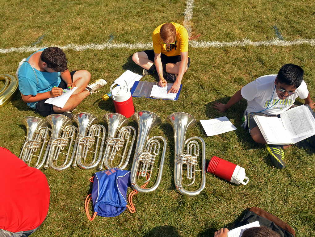 . Members of the North Penn Marching Knight work details during a short break in an afternoon practice.   121 band members are in daily practice at camp as they pepare for the upcoming season that includes a halftime show at Lincoln Financial Field on Thursday, August 28 during the Eagles\'  preseason game against the New York Jets.   The following evening they will have their first community appearance at Crawford Stadium.   Monday,  August 18, 2014.   Photo by Geoff Patton