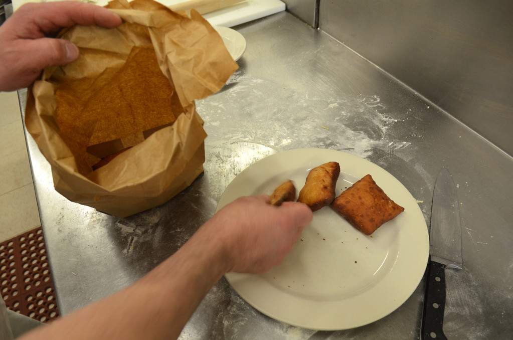 . Fastnachts are loaded into a sugar filled bag for a sugar coating.   Monday, March 3, 2014.  Photo by Geoff Patton
