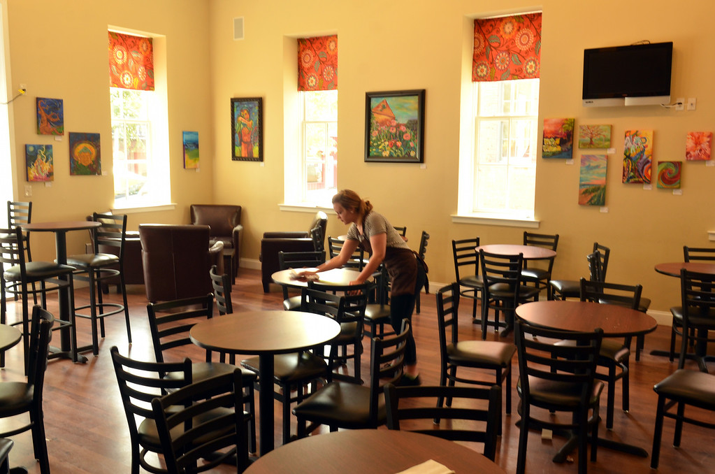 . Employee Rebekah Oliff wipes a tabletop at Main Street Java which will be closing at the end of the month.   Tuesday, August 19, 2014.   Photo by Geoff Patton