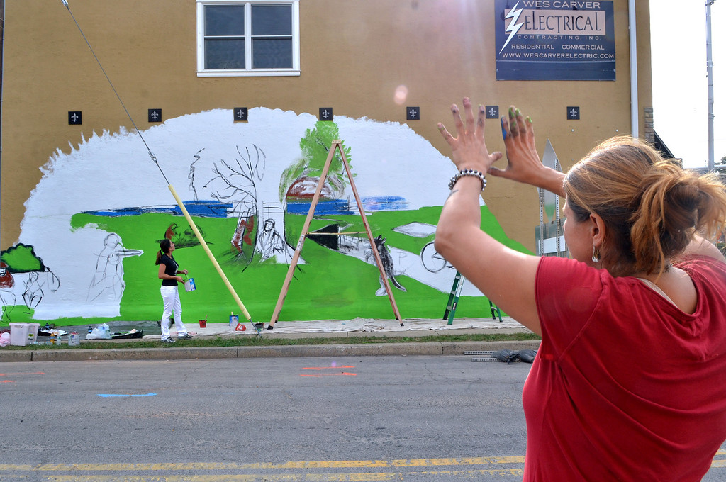""". Artist Karin Wolfe Hendricks (R) and volunteer Kristal Fascella work on her piece titled \""""Seasons\"""" on the wall of Wes Carver Electrical Contracting,Inc. as part of the Lansdale Business Associations Mural Arts Program on Thursday October 3,2013. Photo by Mark C Psoras/The Reporter"""