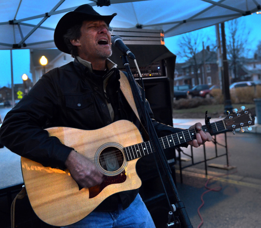 . Jeff Lohan performs songs along Wood Street during First  Friday in Lansdale on a chilly and wet evening  April 4,2014.  (The Reporter/Mark C. Psoras)