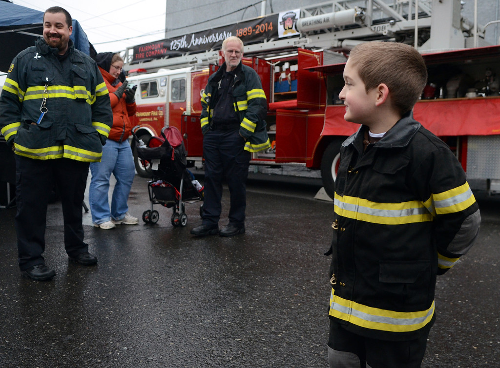 . Fairmount Fire Company President Ian Fickert (L)and his son Aiden (R) check out games and activities during First  Friday in Lansdale on a chilly and wet evening  April 4,2014.  (The Reporter/Mark C. Psoras)