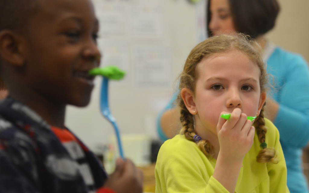 . Students in  teacher Danielle Scheer\'s first grade classroom at Montgomery elelmentary school get a serving of green eggs and ham.   Friday, March 7, 2014.    Photo by Geoff Patton