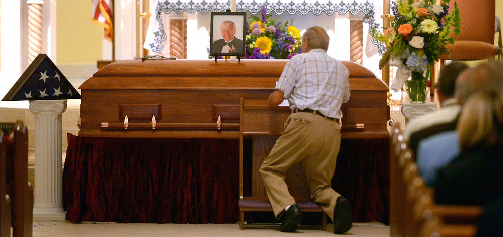". A mourner stops to pay his respects to former Ambler Mayor Charles ""Bud\"" Wahl during the viewing