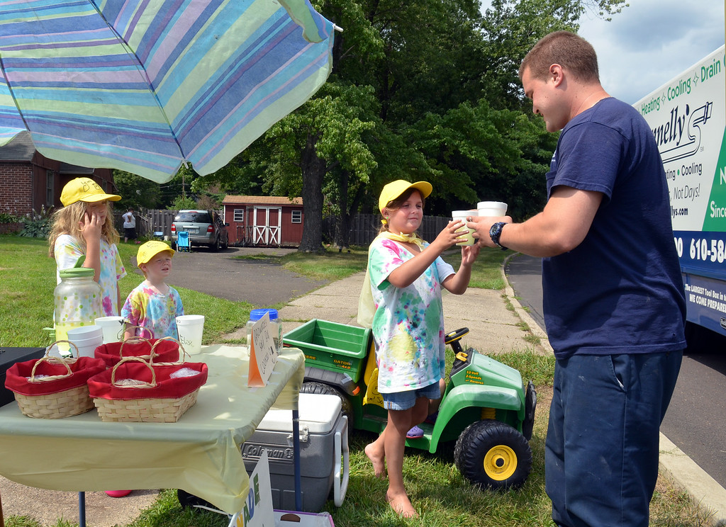 . Jake Hownenstein steps from a  work truck to purchase lemonade from a roadside stand in Lansdale operated by young members of the Wilson and Whiting families who are neighbors on Greenwood Road.   At left is Ella Whiting with her brother Griffin.    Elisha Wilson is at center.   The youngsters combined the first letters of their last names to call the stand  \'W&W Lemonade\'  which also features tie-dyed shirts and yellow hats for the young workers.   They are earning money for their upcoming trip to Wildwood, New Jersey.    Monday,  July  21, 2014.    Photo by Geoff Patton