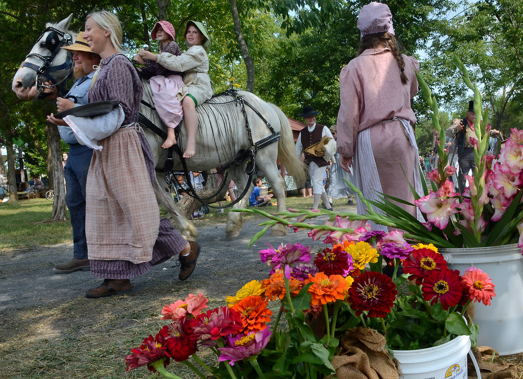 . Sprays of flowers for sale are seen as reenactors take part in the Grand Fantastical Parade around the plantation grounds during the Goschenhoppen Historians\' 48th annual Folk Festival on Friday August 8,2014. Photo by Mark C Psoras