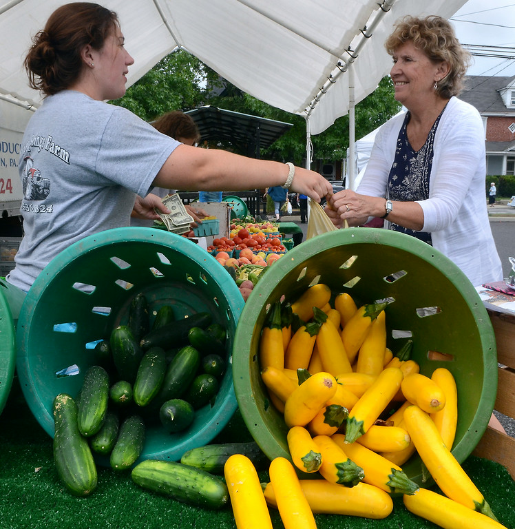 . Fresh produce is purchased from the Windy Springs Farm stand at the Telford Farmers Market on Saturday August 2,2014. Photo by Mark C Psoras/The Reporter